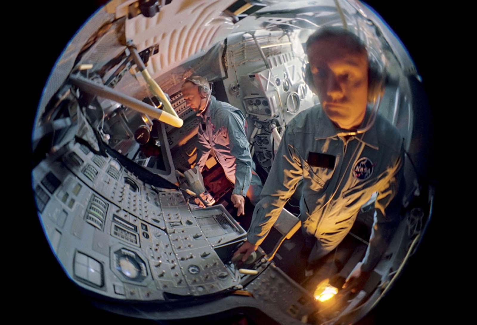 Uma visão de olho de peixe dos astronautas Buzz Aldrin e Neil Armstrong enquanto eles treinam em um módulo lunar.