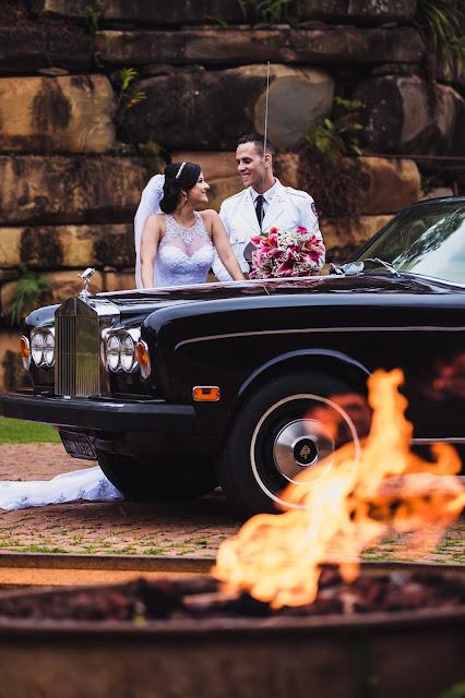 noivos atras do carro roll-royce e na frente a chama de um fogo
