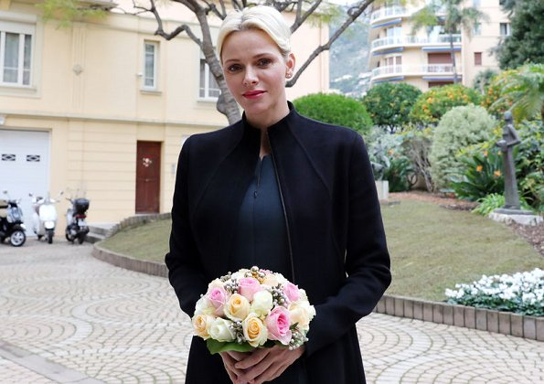 Princess Charlene wore Akris jumpsuit and Akris coat at Monaco Red Cross for Christmas gifts. Christian Dior erarrings