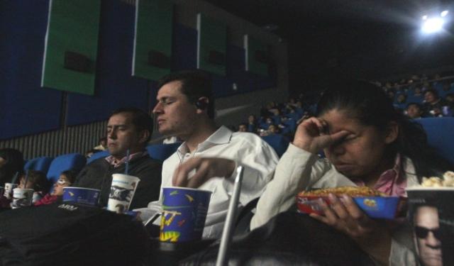 Personas invidentes en una sala de cine, con audiodescripción en sus oídos