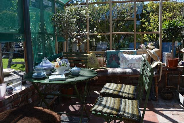 En solrik dag i Cornelias Verden - Sitteplass inne i et vakkert pyntet drivhus