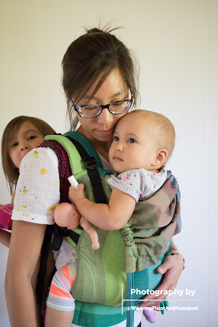Image of a tan skin bespectacled Asian woman smiling down at the toddler worn on her front in a green buckle carrier. On her back is the toddler's older sister in a black and magenta concentric square geometric patterned woven wrap carrier. They're in front of a white wall.