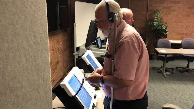 A man with a white cane, wearing headphones, votes using a new machine.