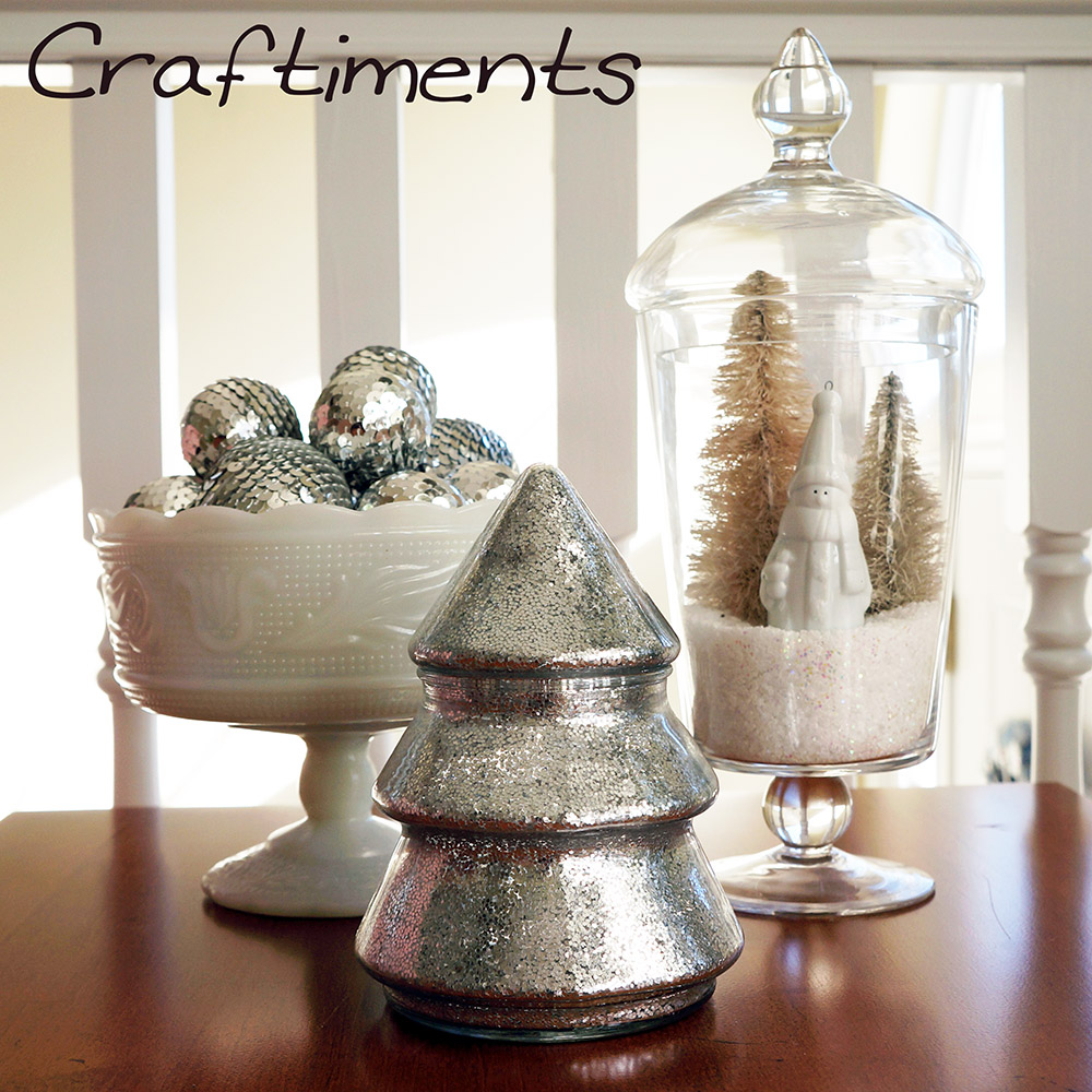 Craftiments:  Glittered tree-shaped candy jar, milk glass dish of sequined balls, miniature winter scene in an apothecary jar