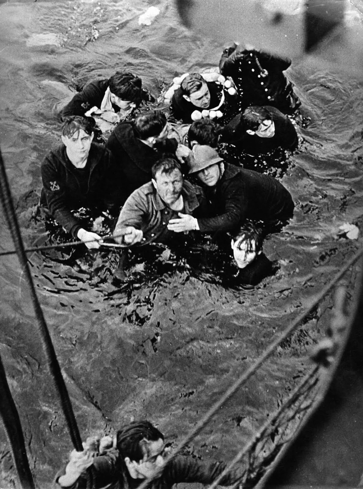 Crew members of the French destroyer Bourrasque, sunk by a mine at Dunkirk, are hauled aboard a British vessel from their sinking life raft.