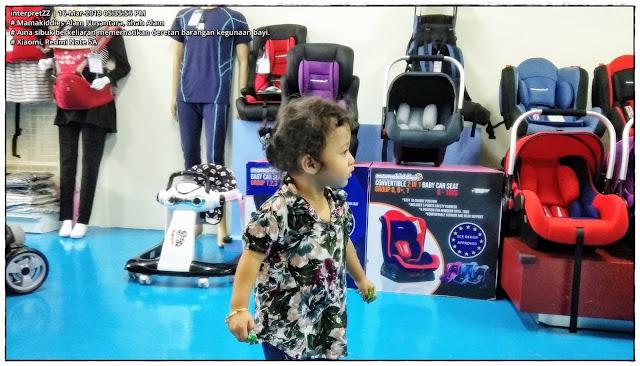 gambar Aina mencari barangan menarik dalam kedai Mamakiddies