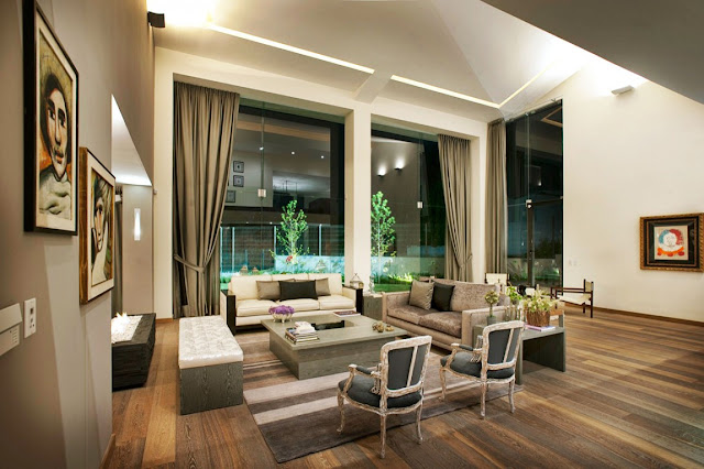 Luxury modern living room with floor to ceiling windows at night