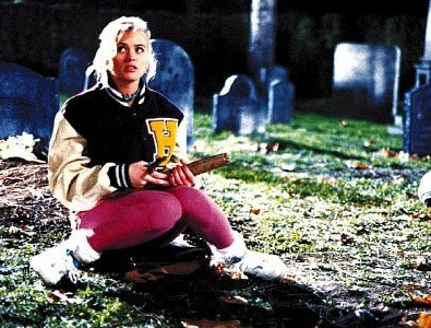 Swanson as Buffy, wearing pink leggings and a varsity jacket, sitting in a graveyard holding a stake
