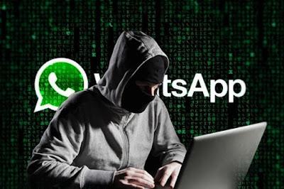 Mascarado diante do computador, com logo do WhatsApp ao fundo