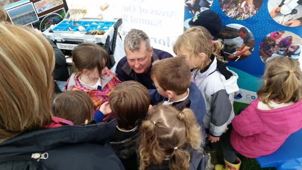 Combe Martin Bioblitz - Dave Edgecombe, surrounded by fascinated children explains the life of limpets