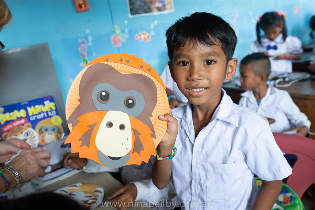 Young Cambodian boy holding up his latest craft creation, a Monkey Mask