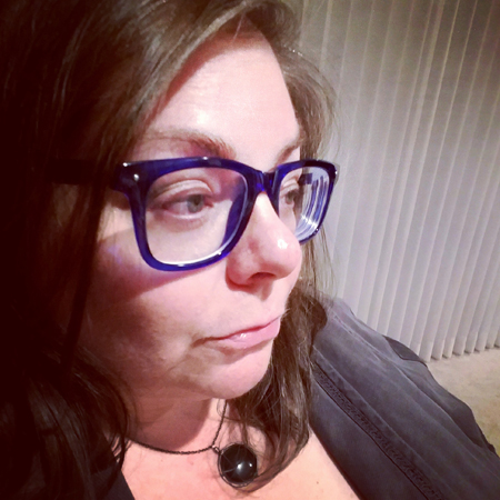 image of me from the shoulders up, in side profile, wearing blue glasses, a black stone necklace, and a grey top