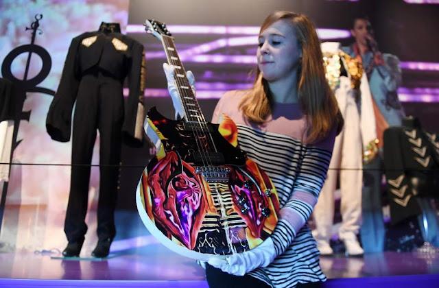 Un miembro del personal de 02 posa con una guitarra que perteneció al artista estadounidense Prince durante la exposición 'My Name is Prince' en el O2 Arena en Londres