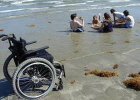 A disabled person on the beach with friends.