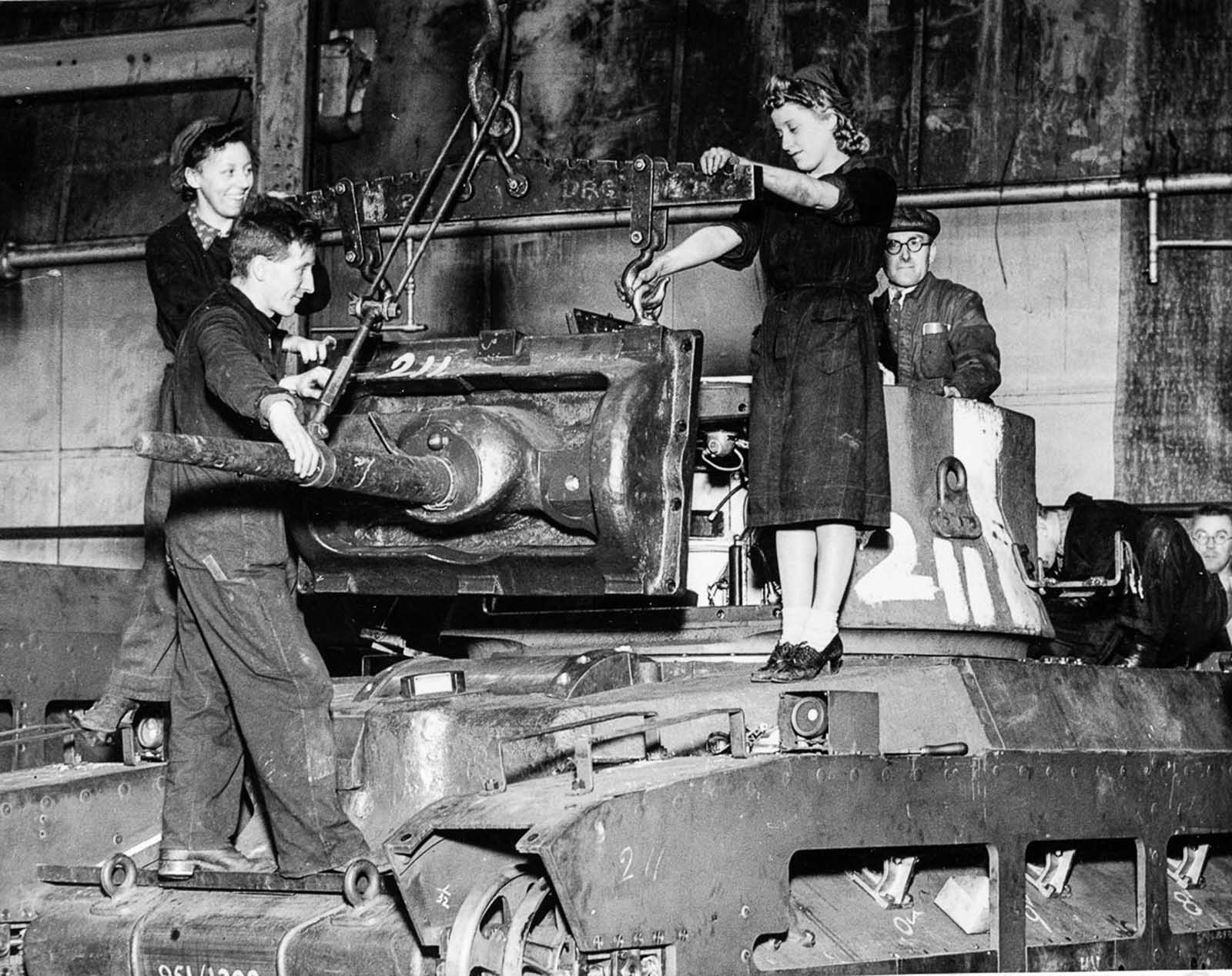 Factory workers in a Ministry of Supply factory fit a gun mounting on a