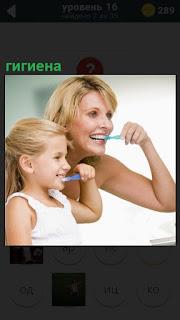 Перед зеркалом в ванной чистят зубы мать и ребенок, соблюдая гигиену