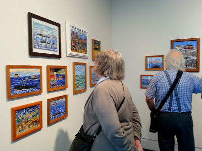 Two people in a gallery, looking at a collection of naive art.