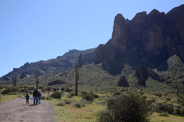 lots of hikers of all ages going to touch the edge of the Superstitions