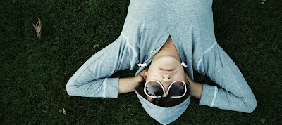 A woman in a gray hoodie and white sunglasses relaxes on green grass