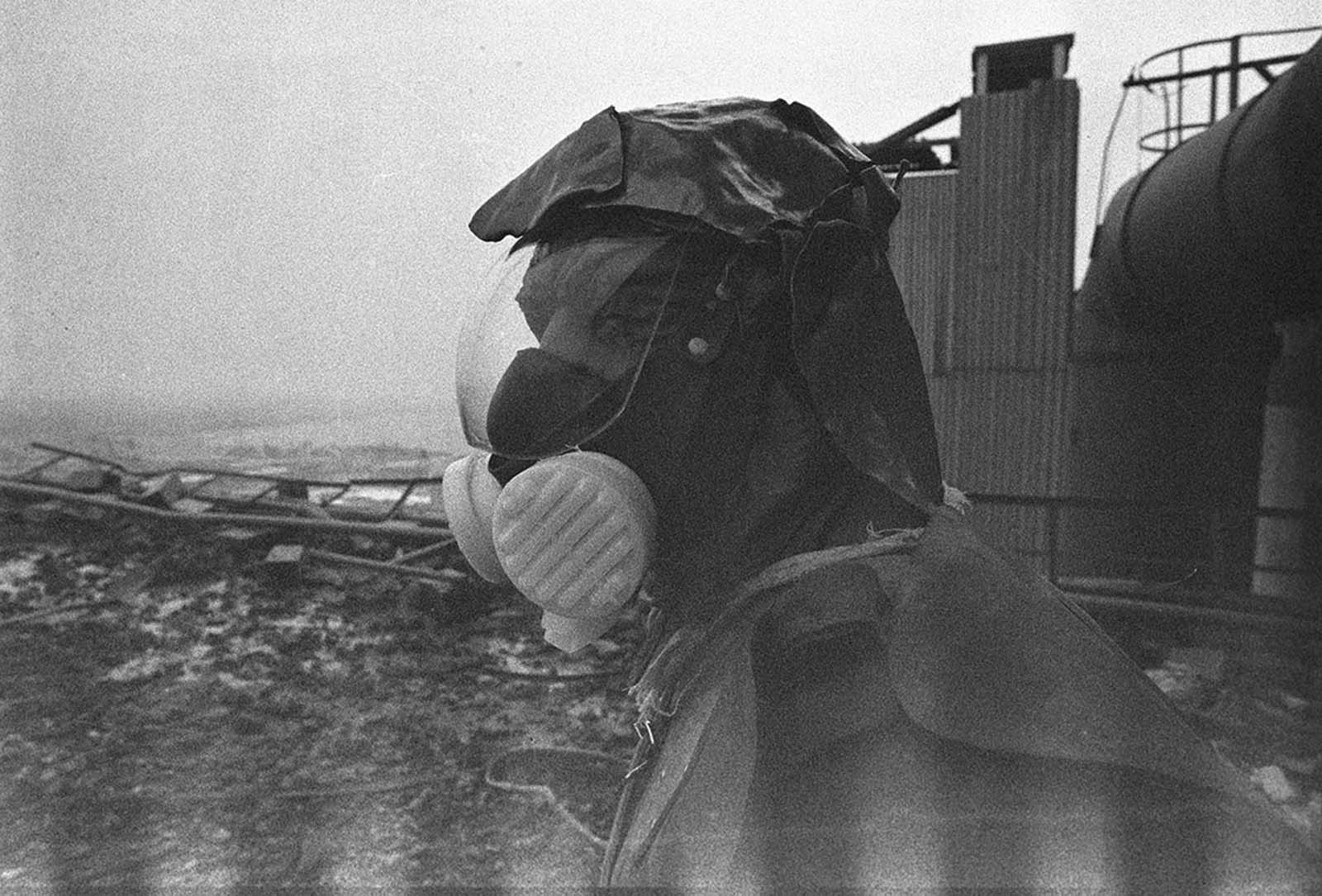 A liquidator, outfitted with handmade lead shielding on his head, works to clean the roof of reactor No. 3.