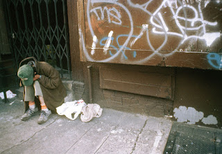 homeless man sits at the steps of a store in lower east side, Manhattan, New York City