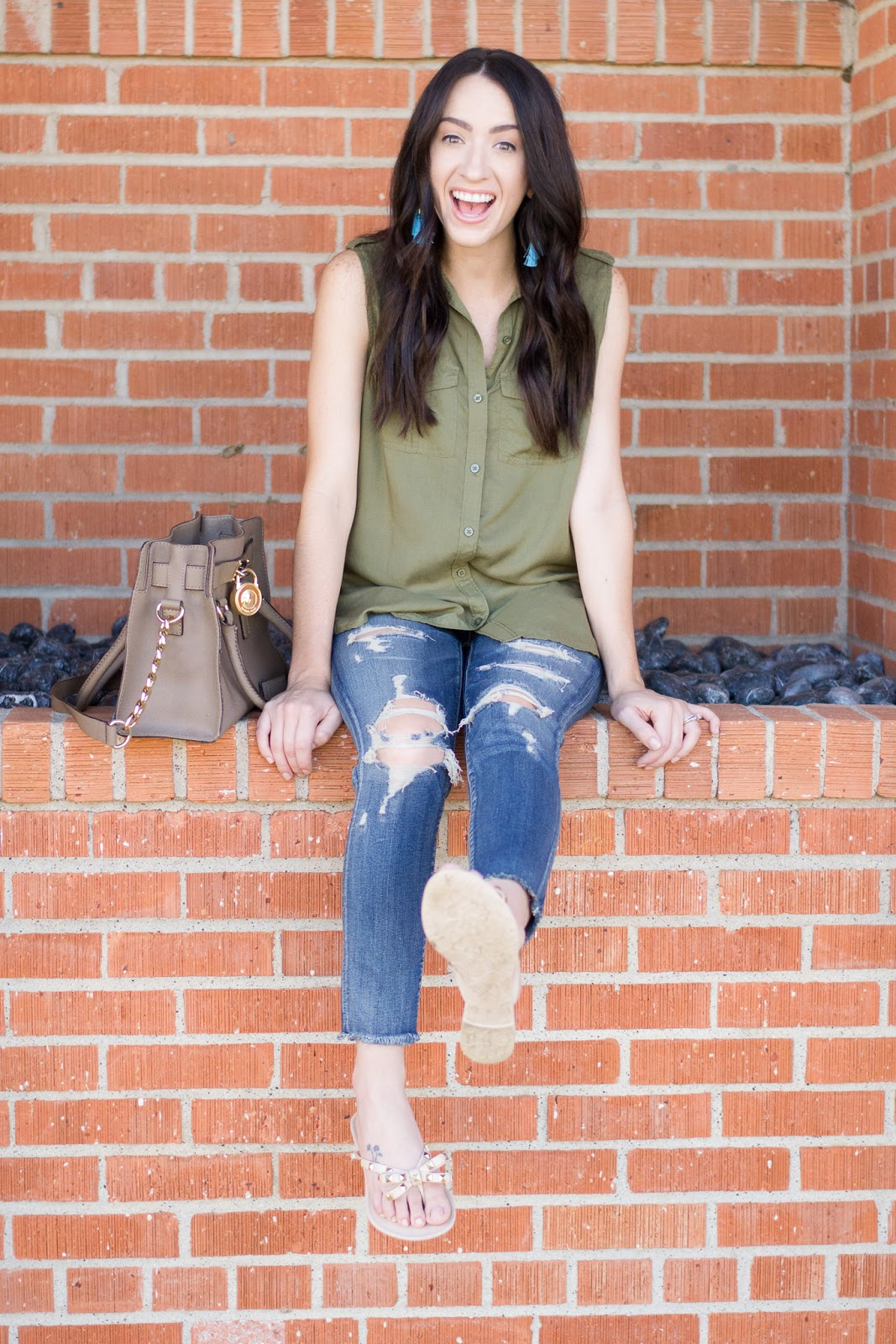 Casual weekend style in ripped denim, button-up tank and tassel earrings