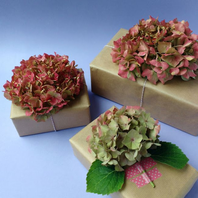 three gifts decorated with hydrangea blooms