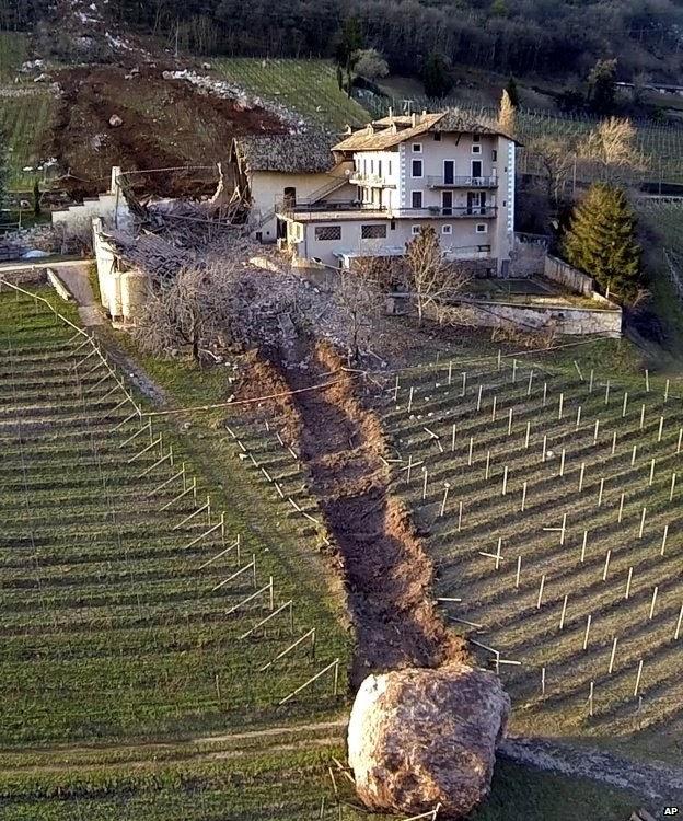 És veu el rastre d'una gran roca que ha caigut rodant d'una muntanya que ha arrasat un bosc i el pati d'una masia en el seu camí. Nord d'Itàlia.