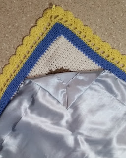 Reverse side of a corner of the blanket with a corner pointing towards the top.  The crocheted blanket is laying with the satin lining on top. The lining is pinned into place but the lining's corner is folded back to reveal the hem.  The crocheted blanket has a yellow border with a scalloped edge. Just inside the edge are filet crochet holes into which a satin ribbon will be woven. The inner border is blue. The corner square is white.