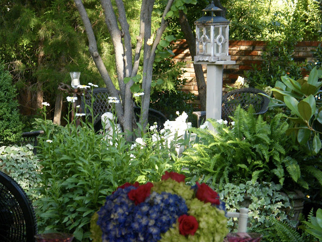 Wooden lantern on wood post stands above garden flowers and foliage.