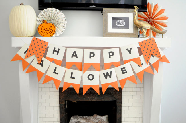 white and orange happy halloween banner on mantel