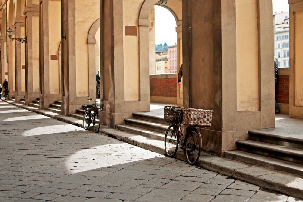 Sous la galerie des Médicis près de l'Arno, deux vélos sont posés sur les colonnes