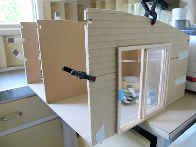 Wall and floor pieces of a doll's house kit taped into place, with siding clamped on and sliding doors installed.
