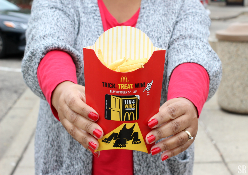 a woman standing next to a McDonald's french fries