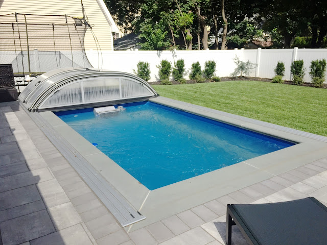 A fully in-ground Endless Pools swimming machine with a retracted pool enclosure