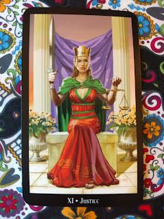 Justice -XI card. Woman with crown, red dress, green cape. On right hand, holds sword pointing up, On left, holds the scales of justice.