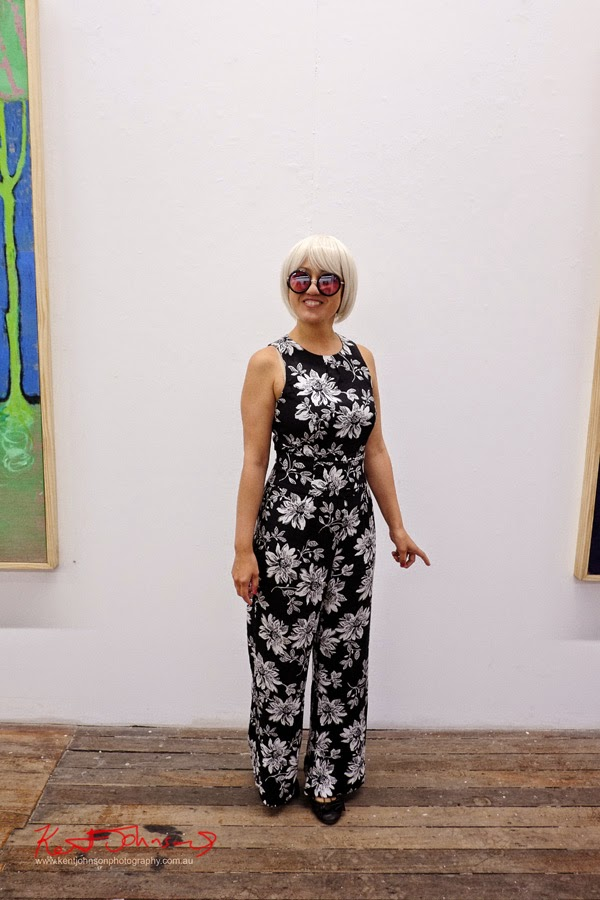 Young woman wearing A black and white floral print jumpsuit and round rose tint sunglasses at Ray Huges Gallery Sydney. Photographed by Kent Johnson.