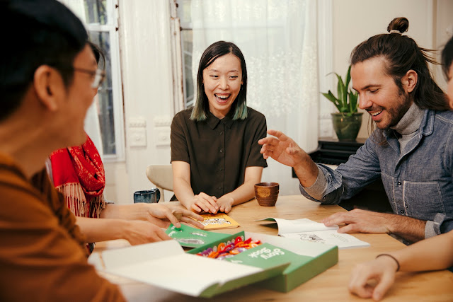 A group of people laughing while playing FlipTales with tokens and cards