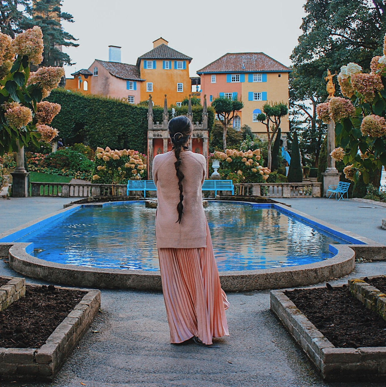 portmeirion wales, seaside places to visit uk, most beautiful village uk, must visit place uk, colourful village uk, indian blogger, london blog, uk travel blogger, all pink look, pink pleated skirt, pale pink outfit, millenial pink outfit, valentines day outfit, long hair styles