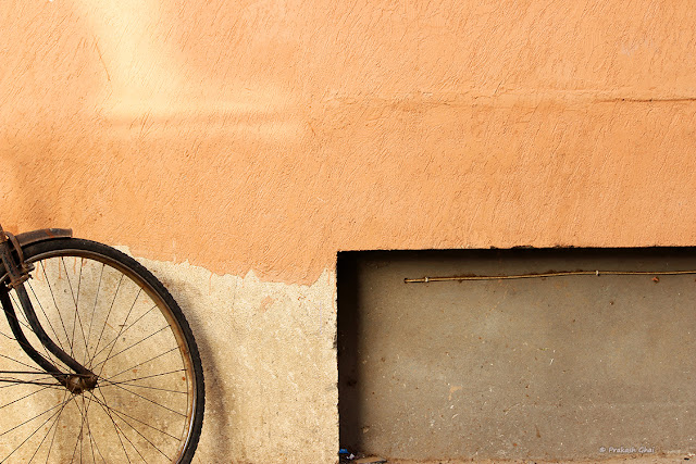 A Minimalist picture of the tyre of a bicycle along with a rectangular cut on a textured Indian wall.
