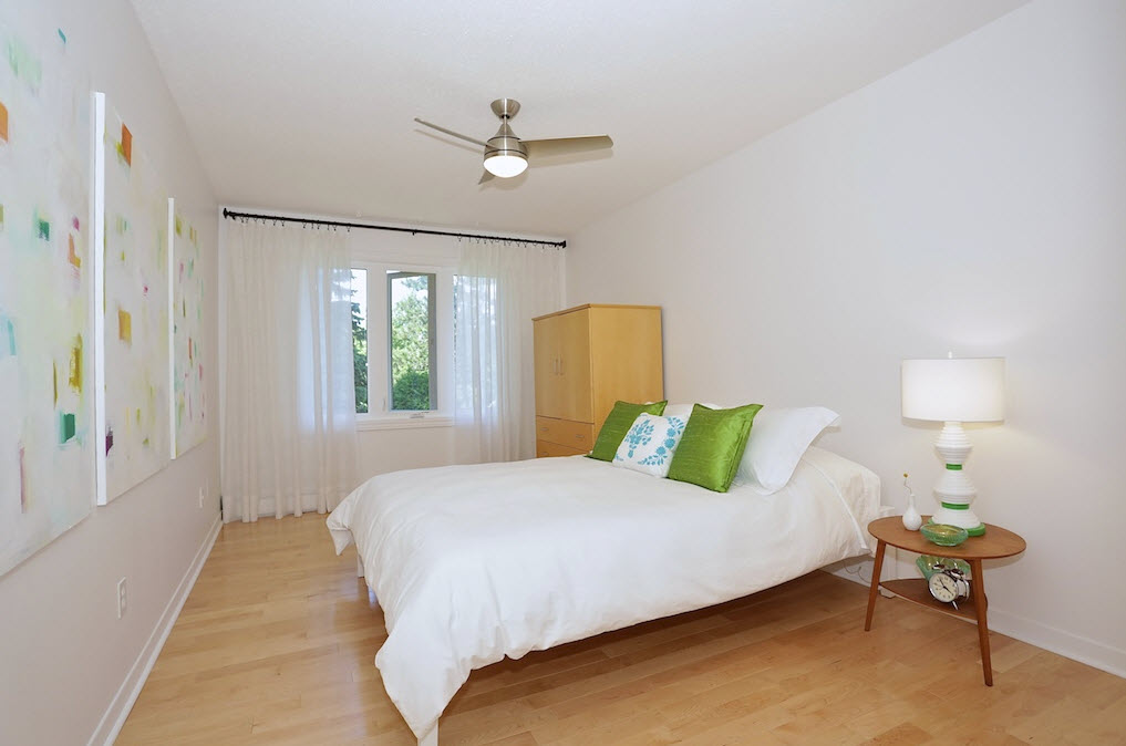 Airy bedroom with white linens and maple wood floors