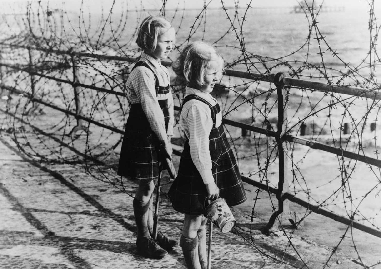 Two girls on the south coast of England look out toward the beach through a barbed wire fence constructed as part of Britain's coastal defenses.