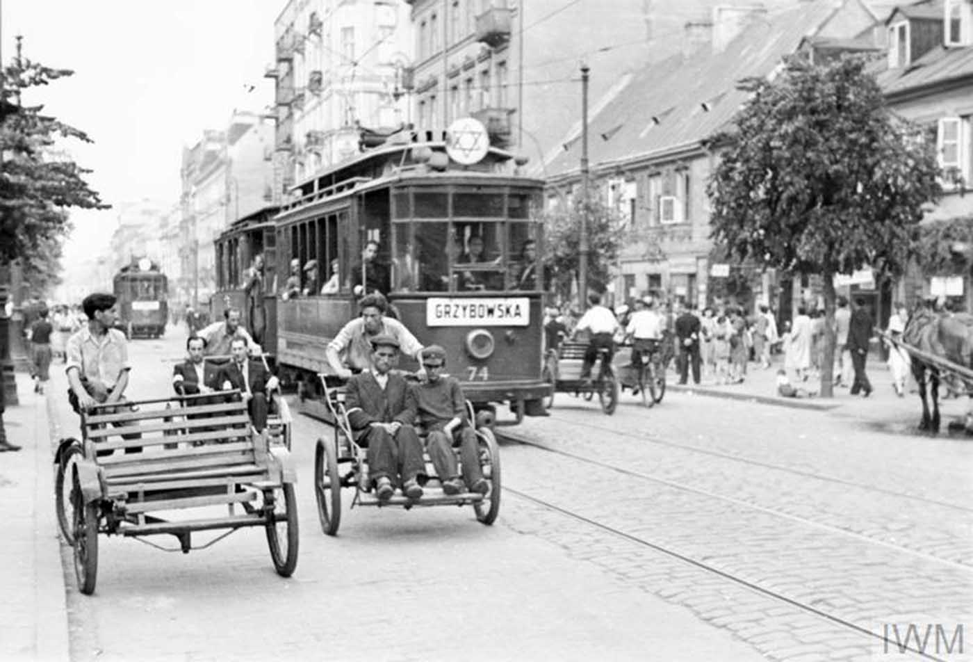 Street rickshaws and a tramcar carrying passengers along Leszno Street in the ghetto, summer 1941. This particular tramline was run between the Muranowski Square and the Grzybowska Street. The plaque on the tram indicates it runs towards Grzybowska Street.