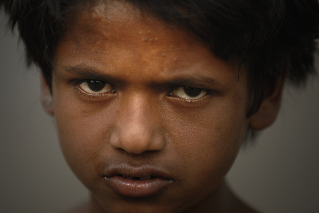 Photo of a child beggar boy in New Delhi, India.