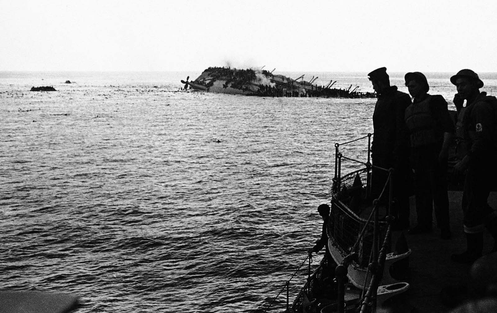 The dramatic and tragic scene as the Cunard White Star liner Lancastria was sunk on August 3, 1940. The Lancastria was evacuating British nationals and troops from France, and had boarded as many as possible for the short trip - an estimated 4,000 to 9,000 passengers were aboard. A German Junkers 88 aircraft bombed the ship shortly after it departed, and it sank within twenty minutes. While 2,477 were rescued, an estimated 4,000 others perished by bomb blasts, strafing, drowning, or choking in oil-fouled water. Photo taken from one of the rescue boats as the liner heels over, as men swarm down her sides and swim for safety to the rescue ships. Note the large number of bobbing heads in the water.