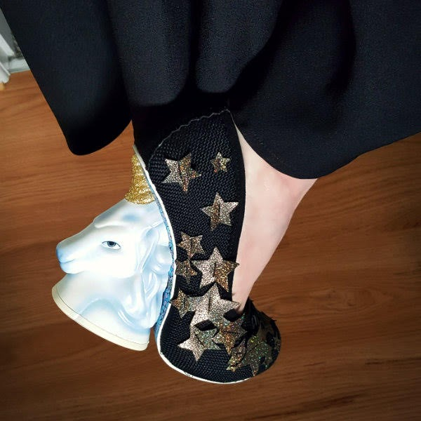 close up wearing black unicorn heeled shoes with holographic stars