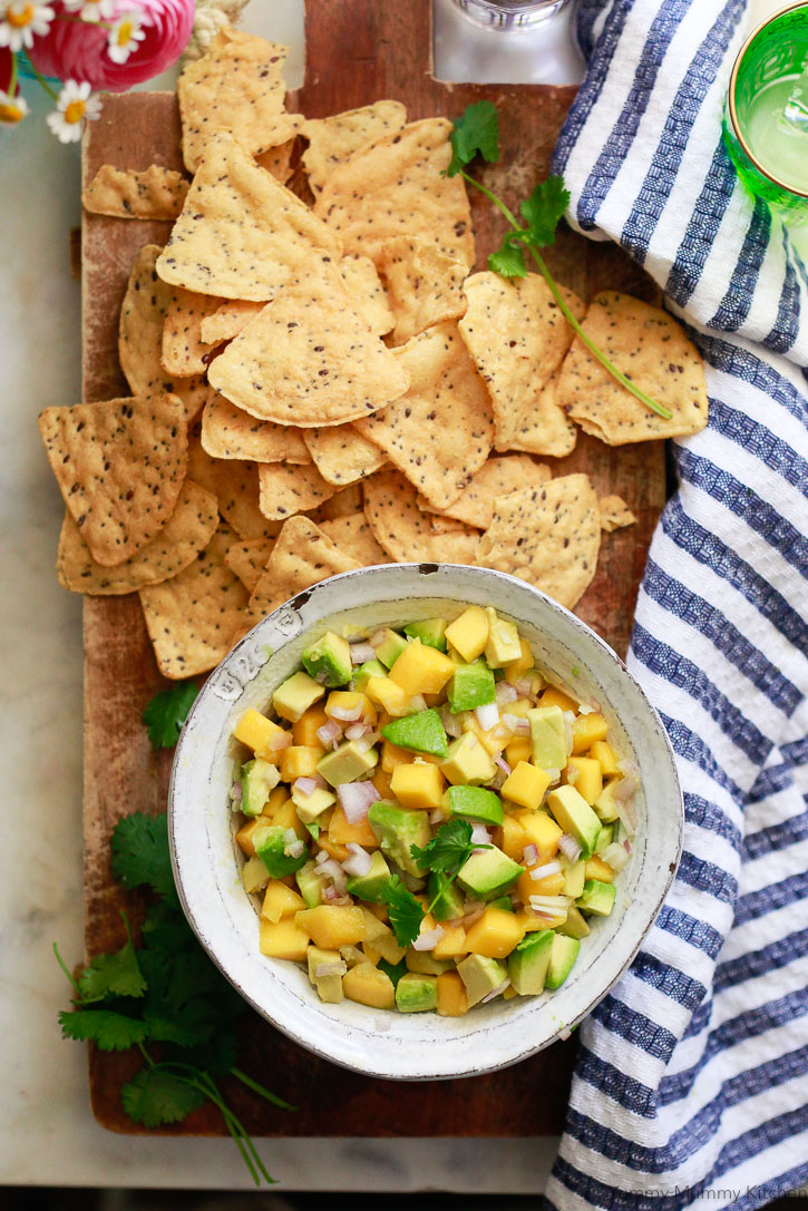 A bowl of fresh homemade mango avocado salsa with flax chips.