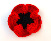 Crocheted poppy. Black centre has 5 blunt points around which are rounded red petals which overlap each other and curl upwards.