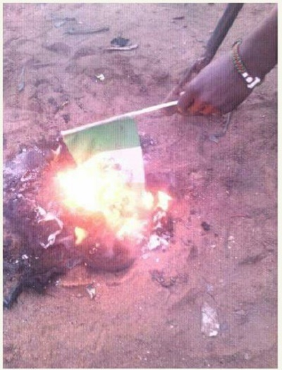 Oh No!!! Man Brings Out His Manhood, Urinates on Nigerian Flag and Burns It (Photos)