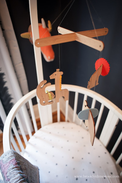 Wooden animal mobil over white crib in safari nursery